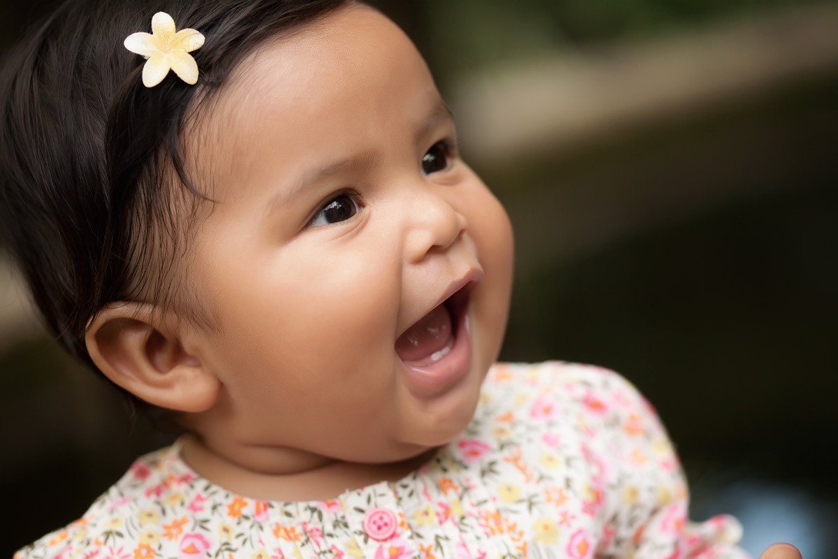 smiling hispanic baby with flower in her hair