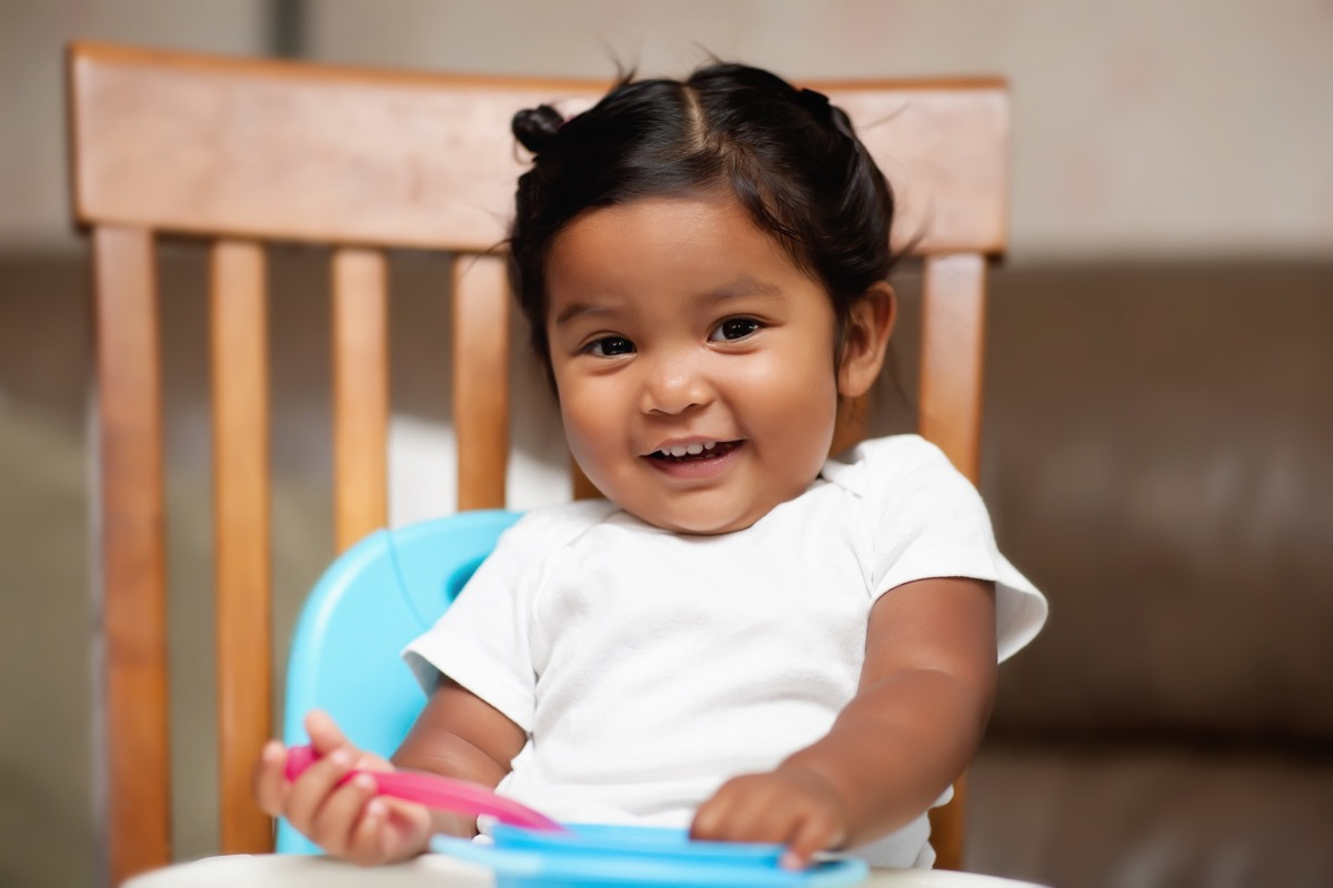 cute baby girl sitting in high chair