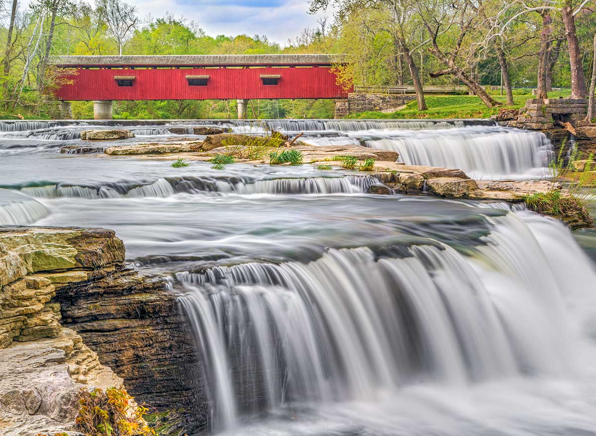waterfall with a red covered bridge in the background