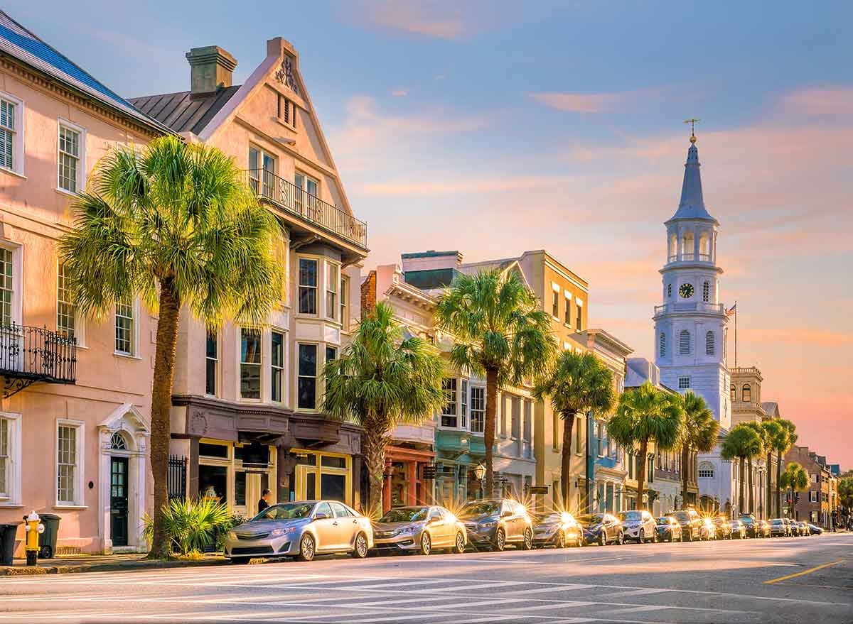 palm trees line storefronts and a church in charleston