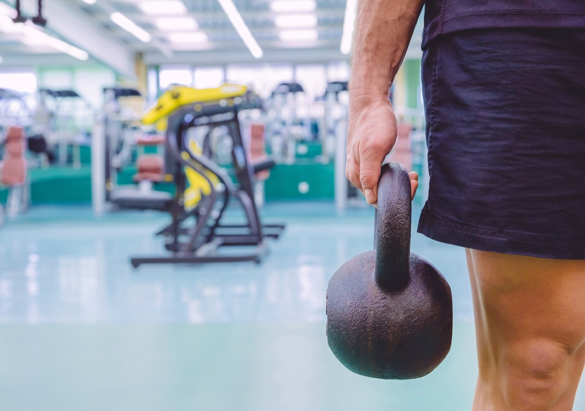 Man holding kettlebells at the gym