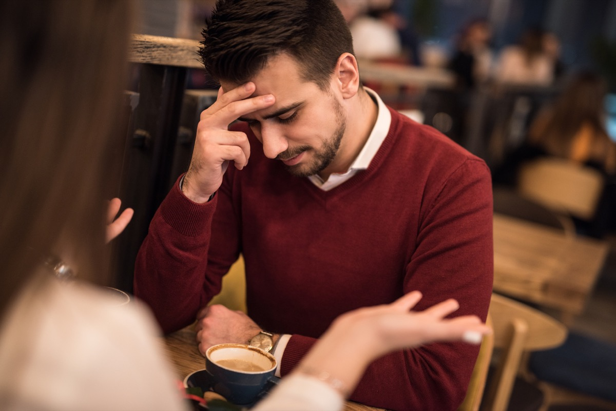 man looking down and touching his forehead while woman talks at a coffee shop