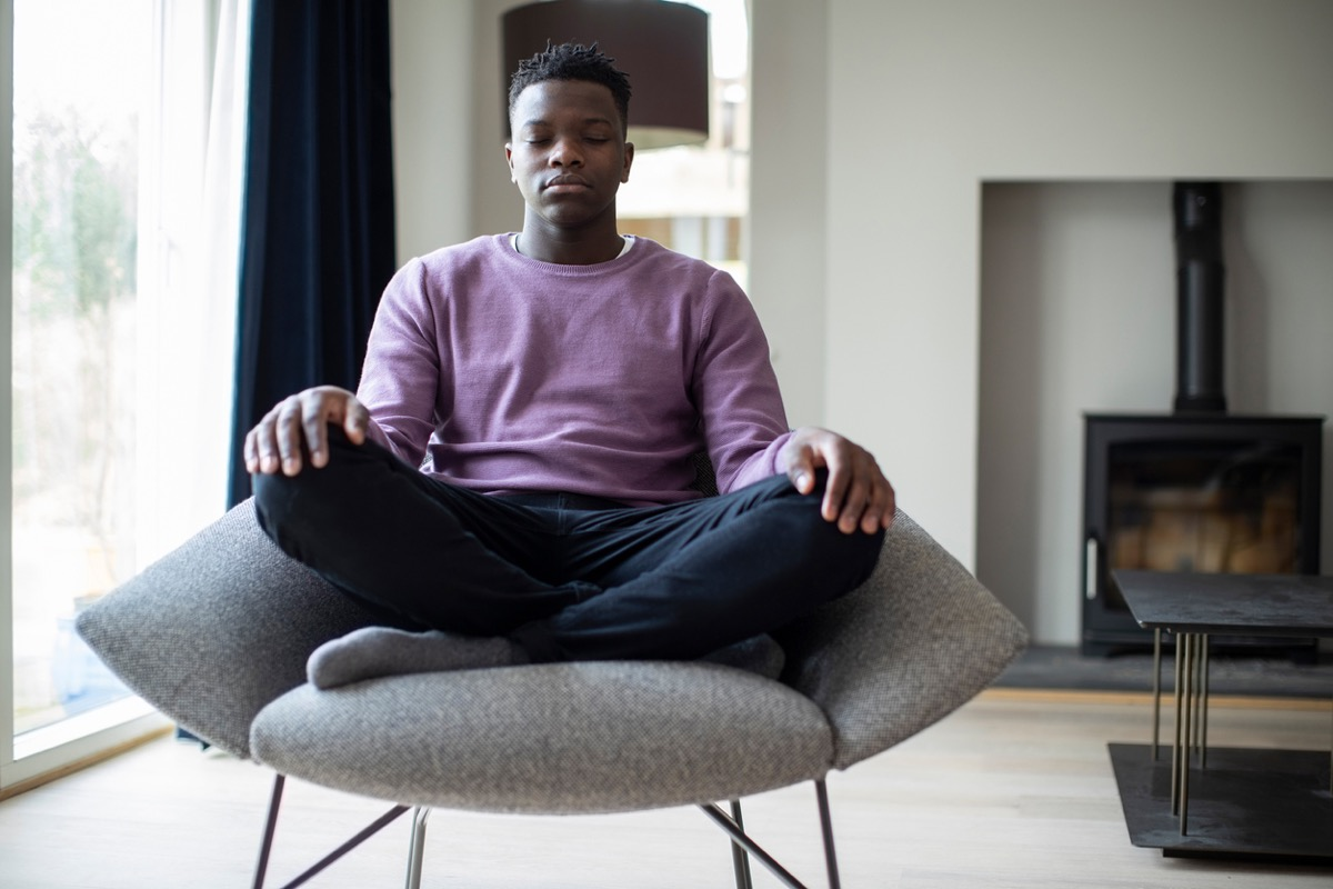 young black man meditating in a chair