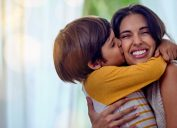 Shot of an adorable Latinx little boy affectionately kissing his mother at home while hugging her
