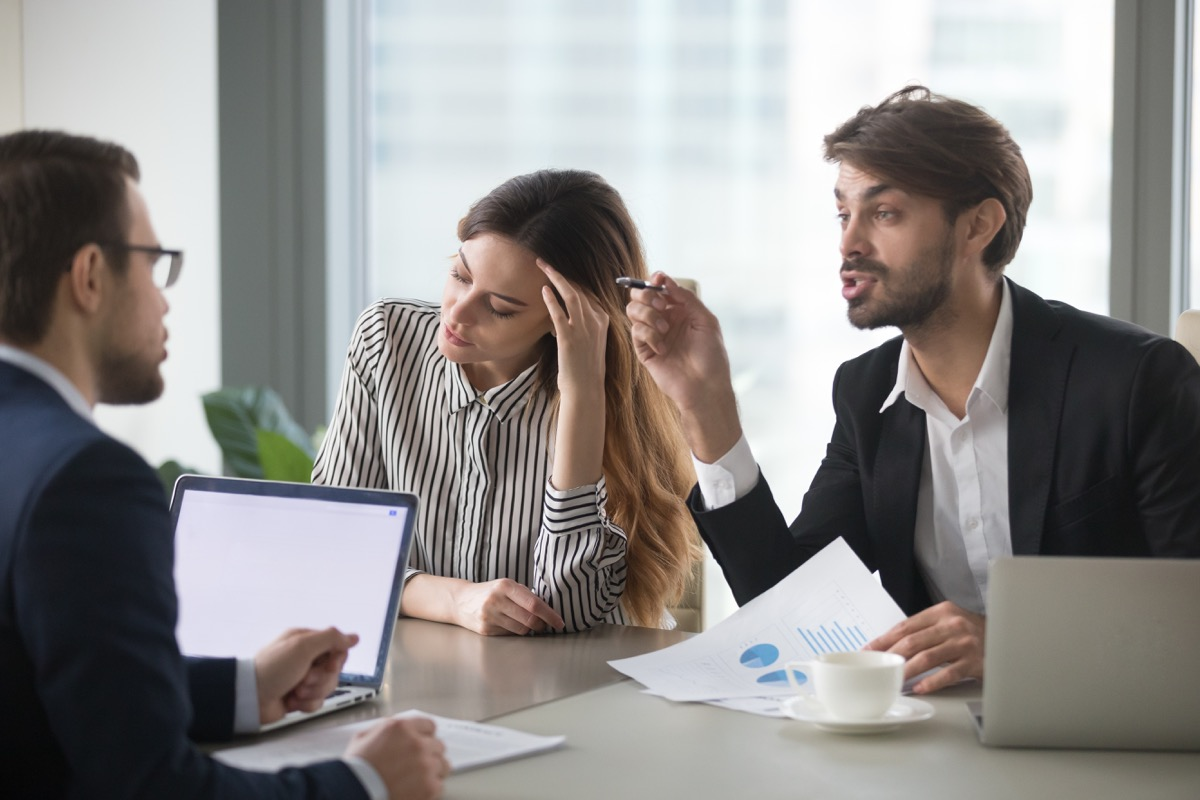 Man interrupting woman talking in business meeting with colleague