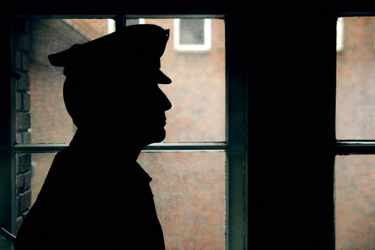 warder's silhouette, prison walls outside the window.