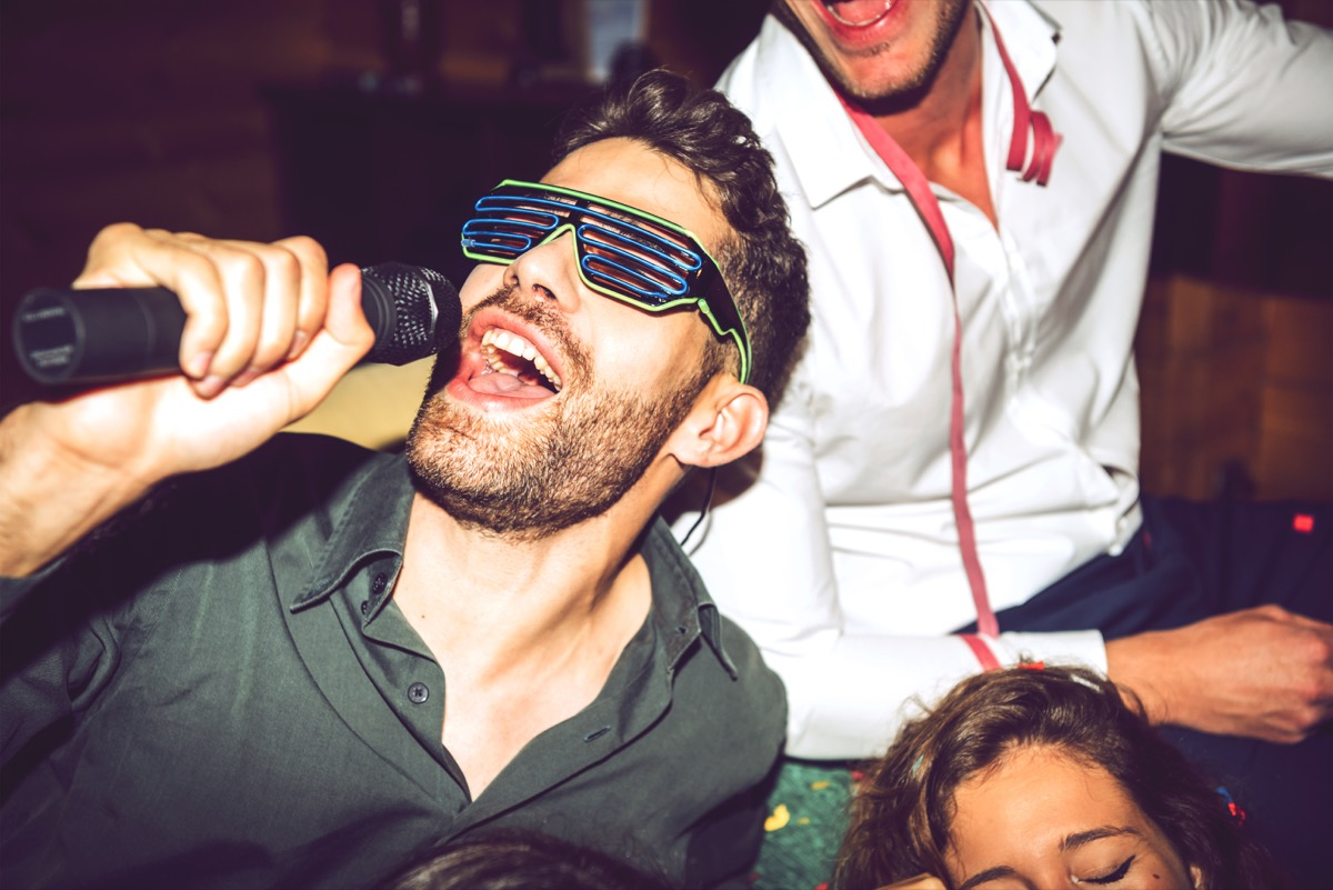Man singing karaoke with friends