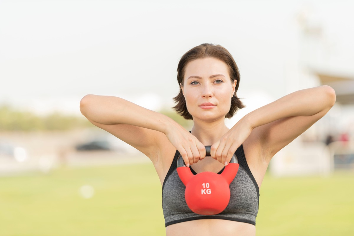 Woman using a kettlebell to do an upright row