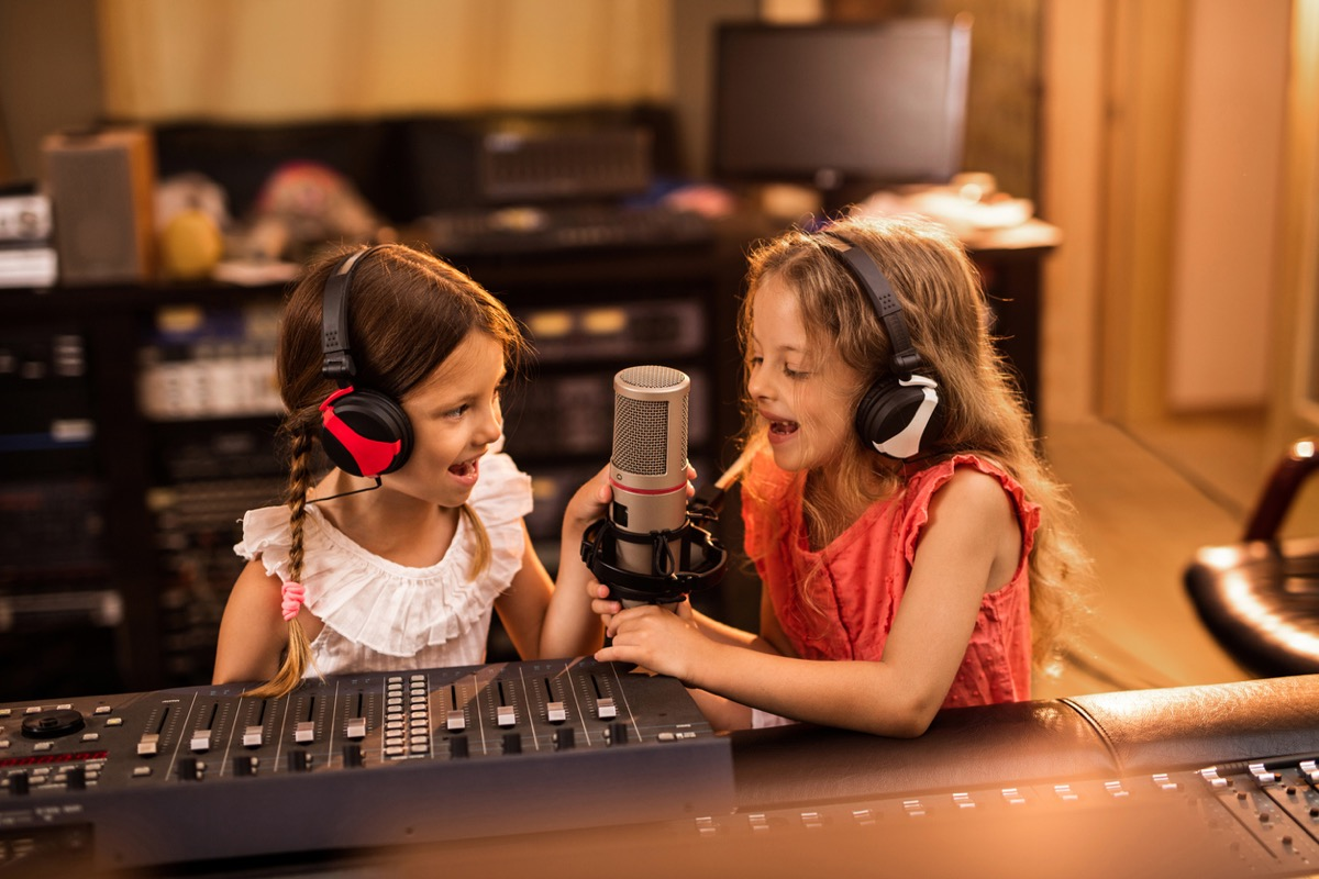 Two small girls having fun in a radio station while talking on a microphone for a podcast