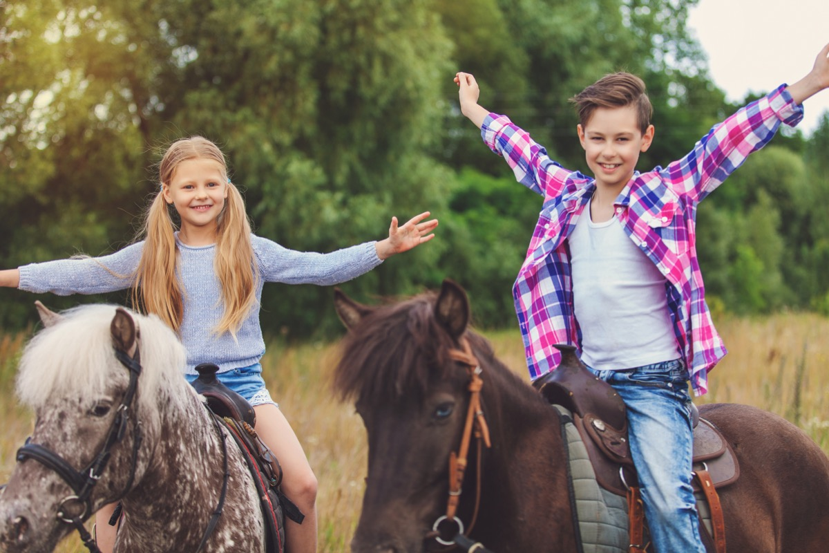 Kids riding horses excited