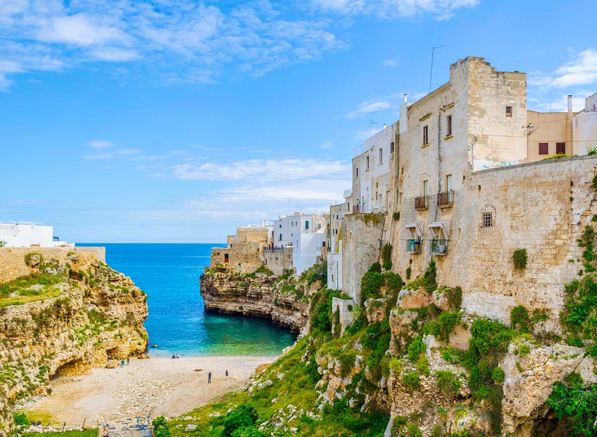 a cove of turquoise water with italian buildings on the side