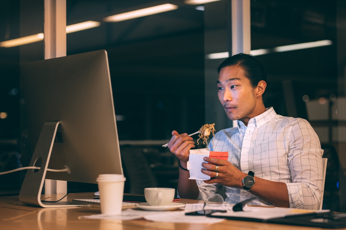 Man eating a late dinner at his desk
