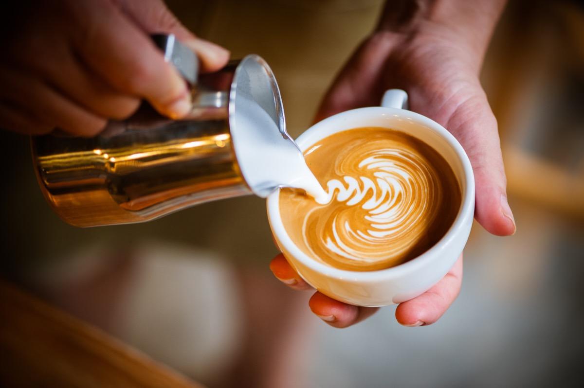 Barista making latte swirl art with golden creamer