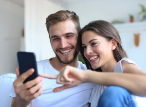 Couple looking and laughing at phone on couch