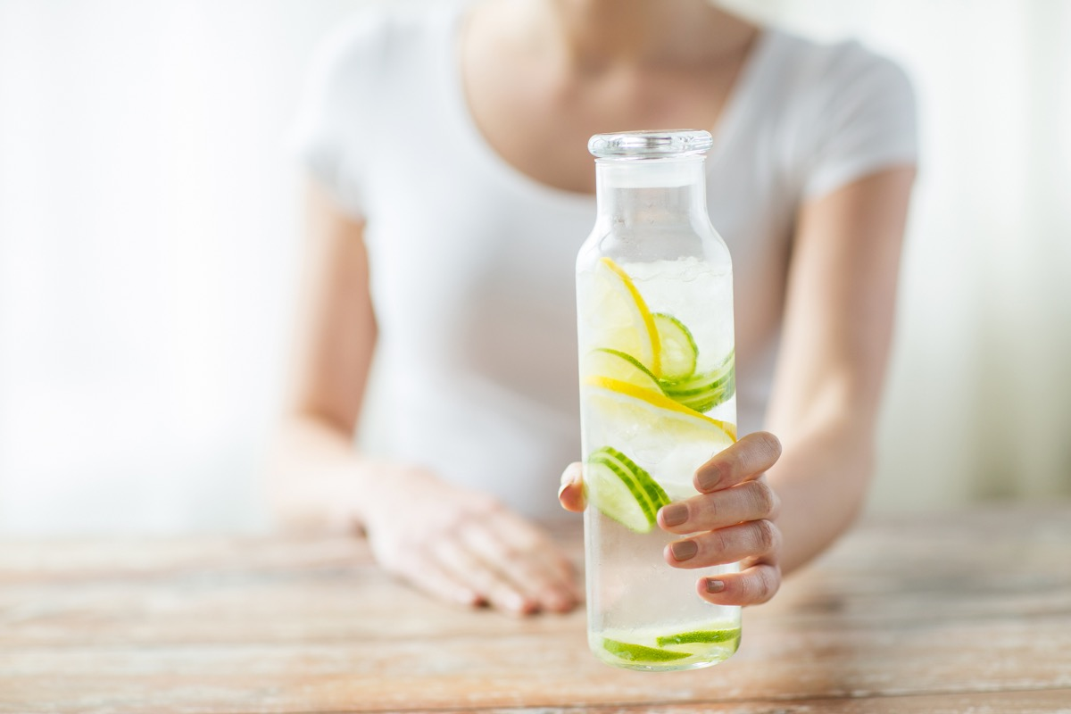 Woman holding a glass bottle of refreshing lemon and cucumber infused water