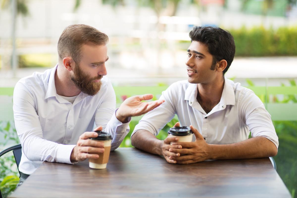 Male friends talking over coffee