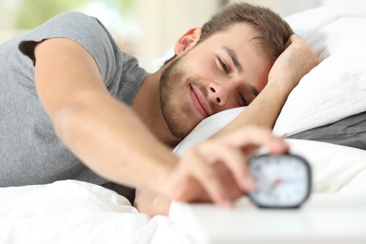 Man turning off his alarm clock