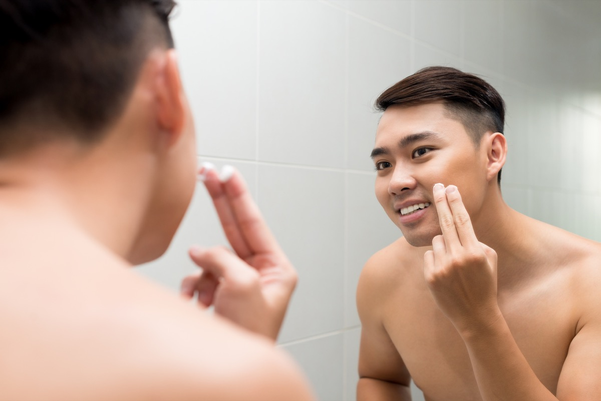 Young Asian man applying facial lotion in front of the mirror