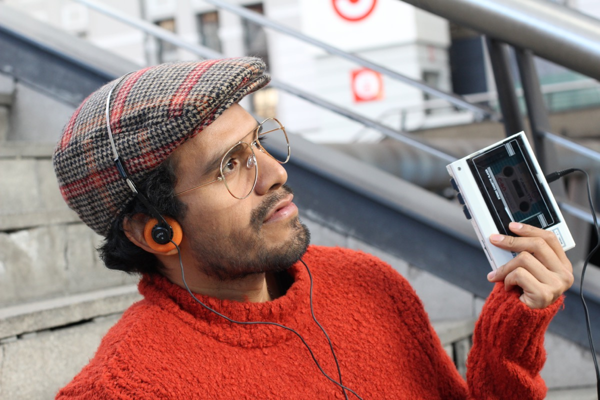 Retro-looking man listening to music on a old school tape recorder