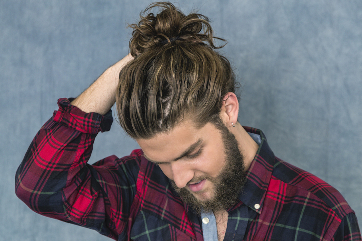 Portrait of a young man with long, tousled brown hair and a full beard wearing a plaid lumberjack shirt and adjusting his bun