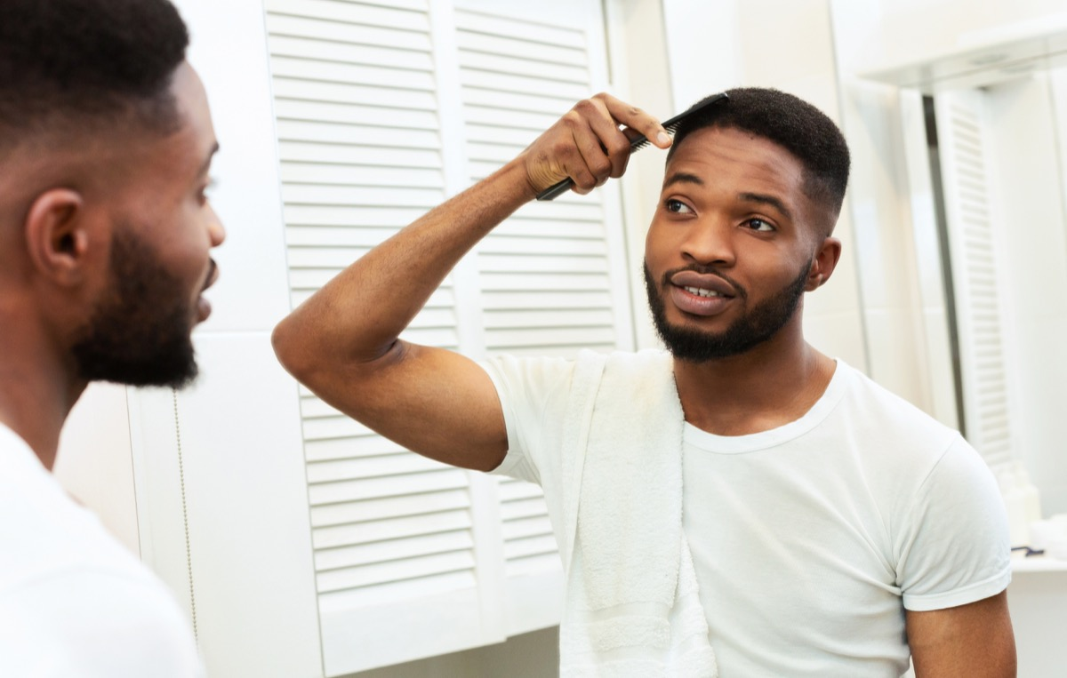 Man combing his hair in the mirror