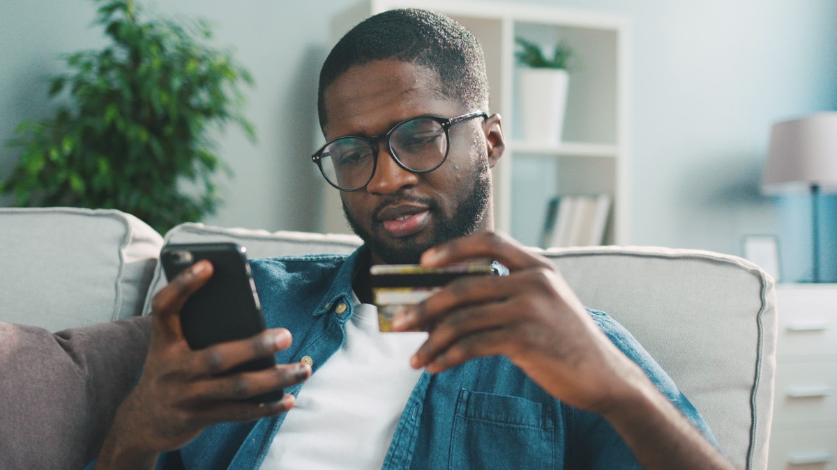 Man holding his credit card and his phone