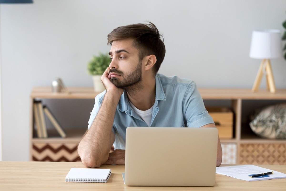 Man looking around distracted at work
