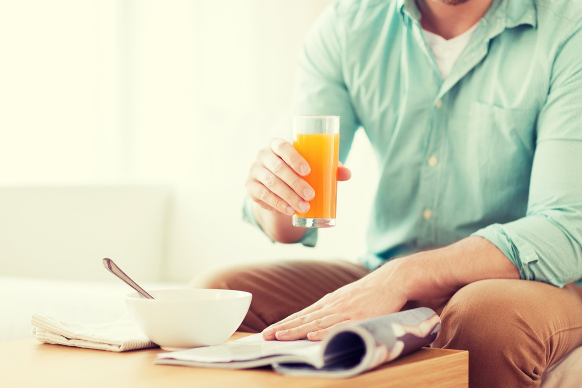 Man drinking fruit juice while he reads the paper and eats breakfast
