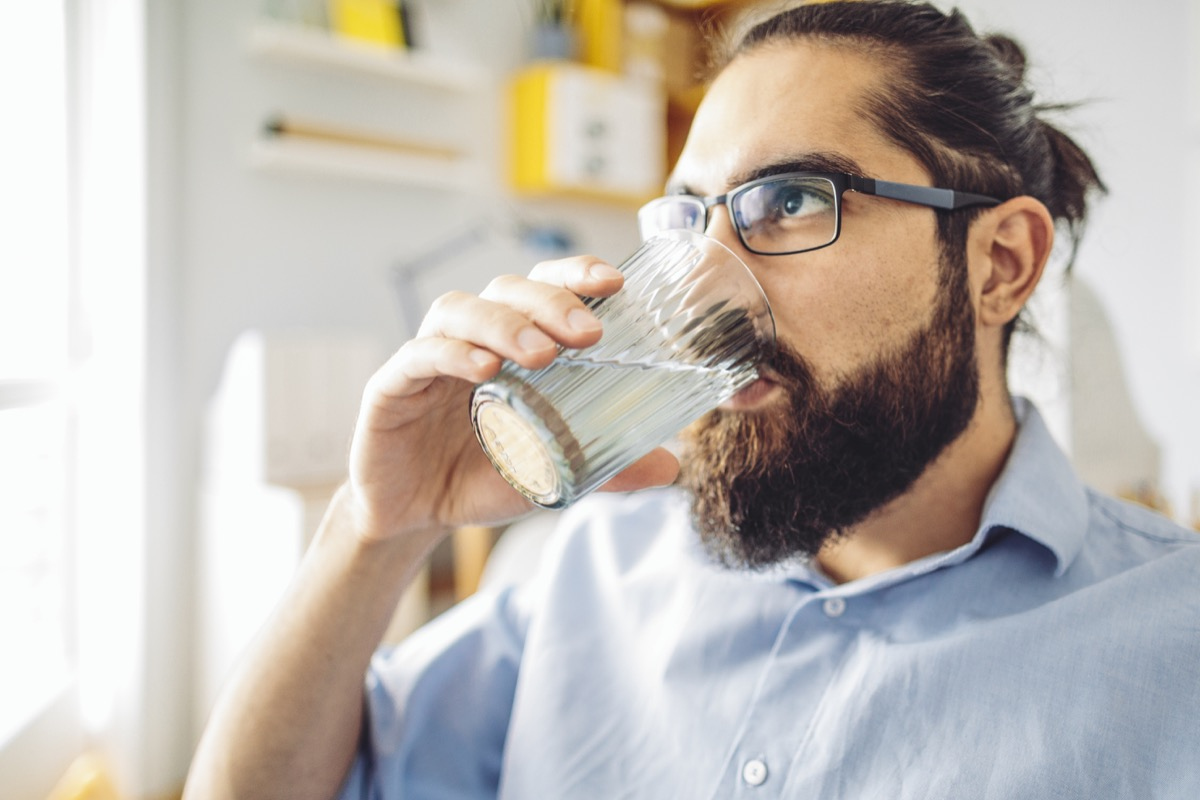 Man with a man bun and glasses drinking water at home