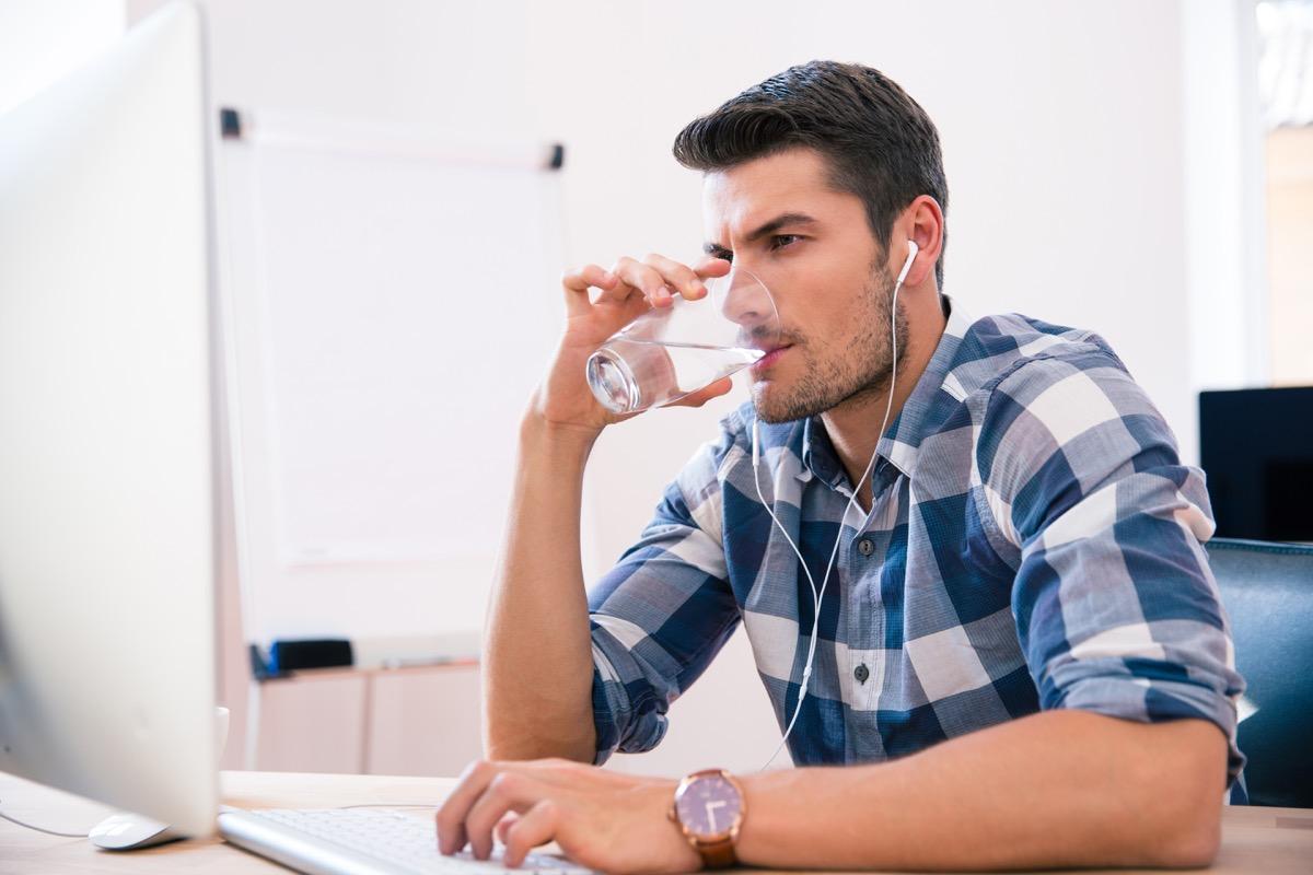 Man drinking water at work