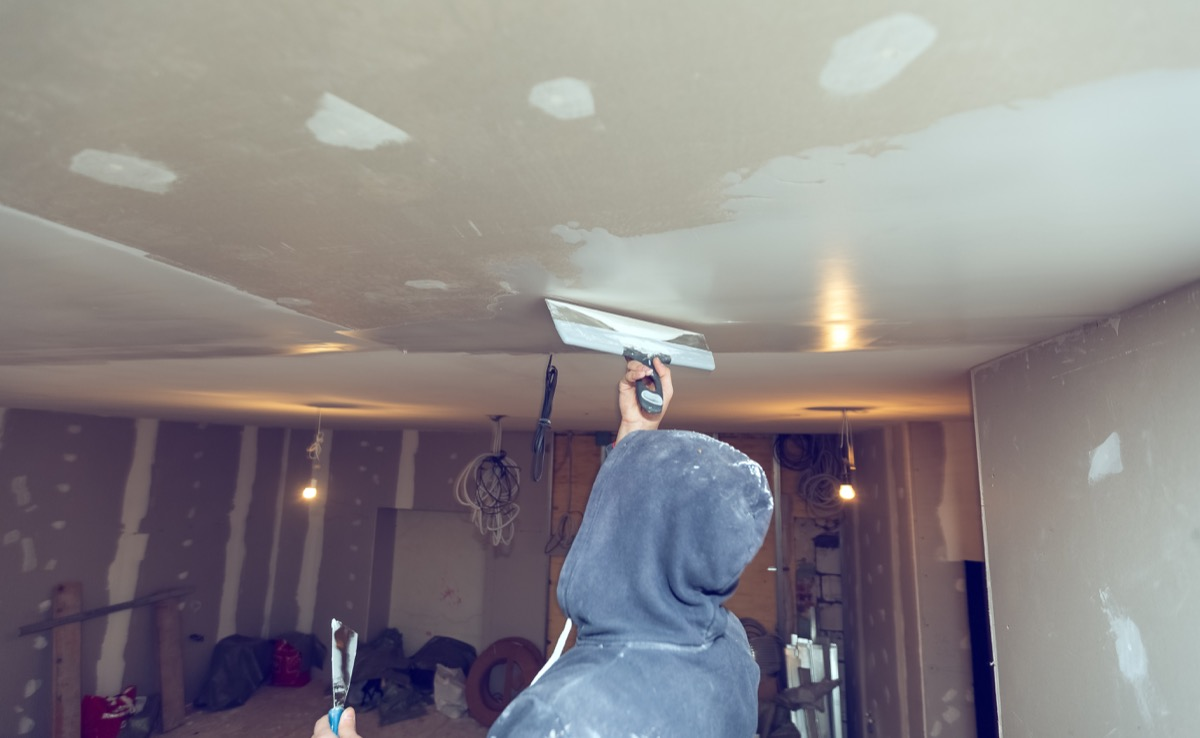 person in hoodie skim coating a drywall ceiling in unfinished room