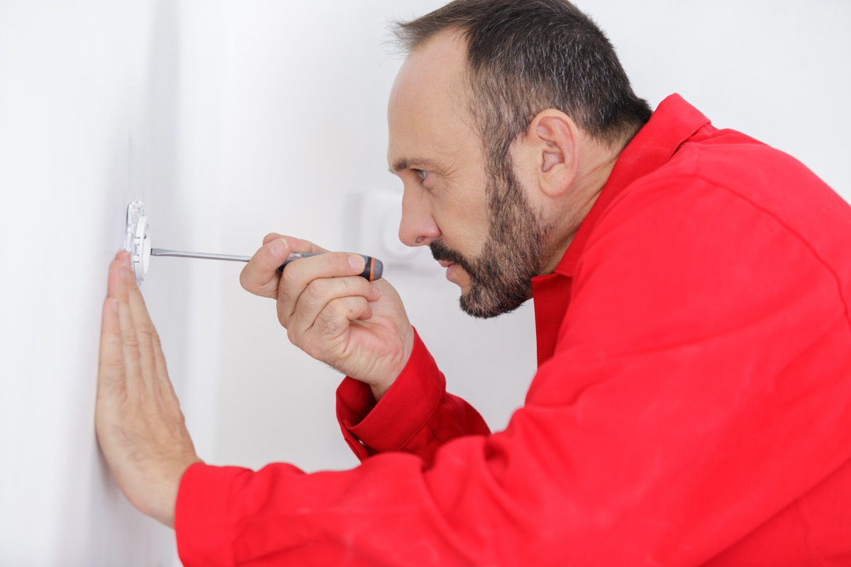 white man fixing outlet