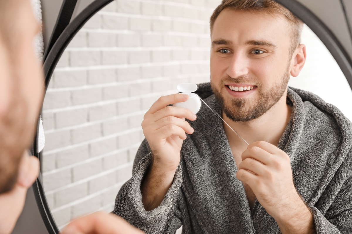 Man in a robe flossing in the mirror