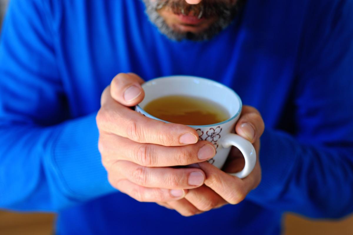 Bearded man drinking green tea from a mug