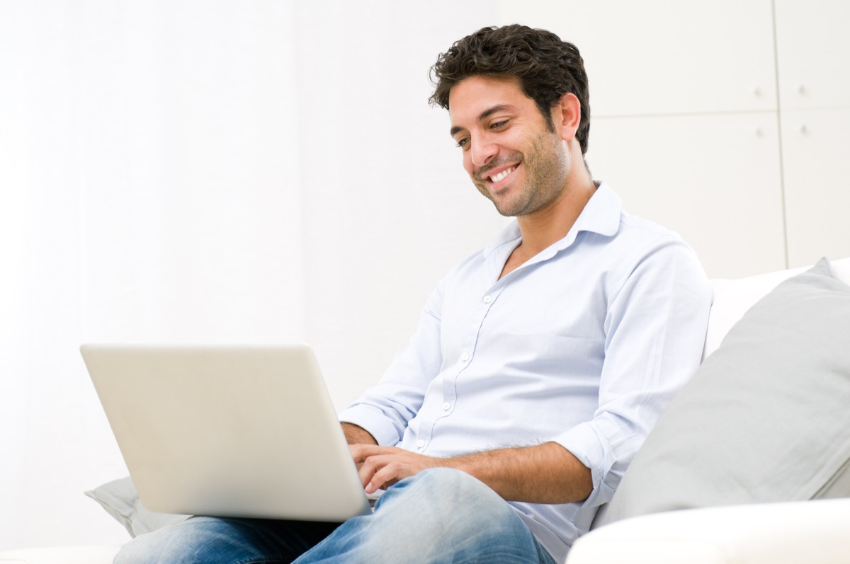 Man happily doing work on his laptop at home