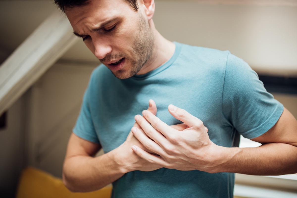 Young man holding his chest in pain