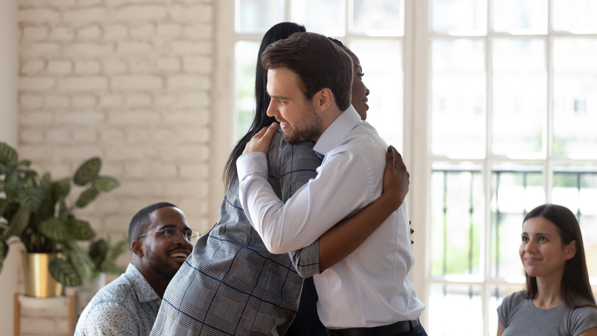 young white man hugging black female coworker