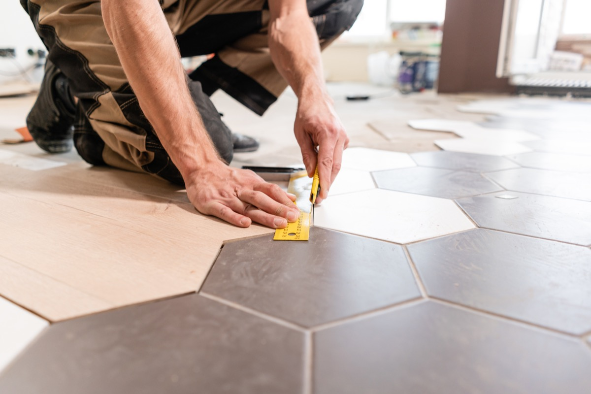 Professional man installing tile on the floor