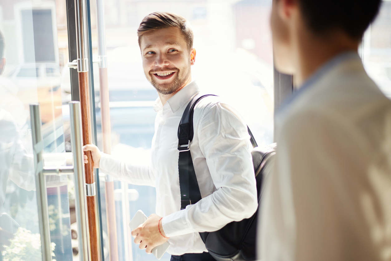 young man with backpack walking out of cafe door during conversation