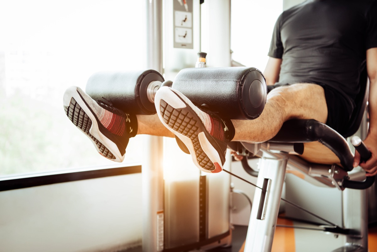 Man using the leg extension machine at the gym