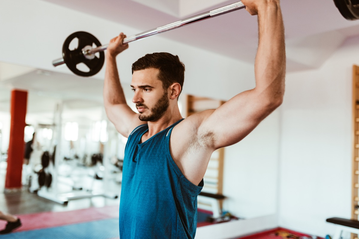 man using the barbell at gym