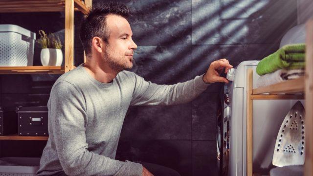 man looking at washing machine setting the presets