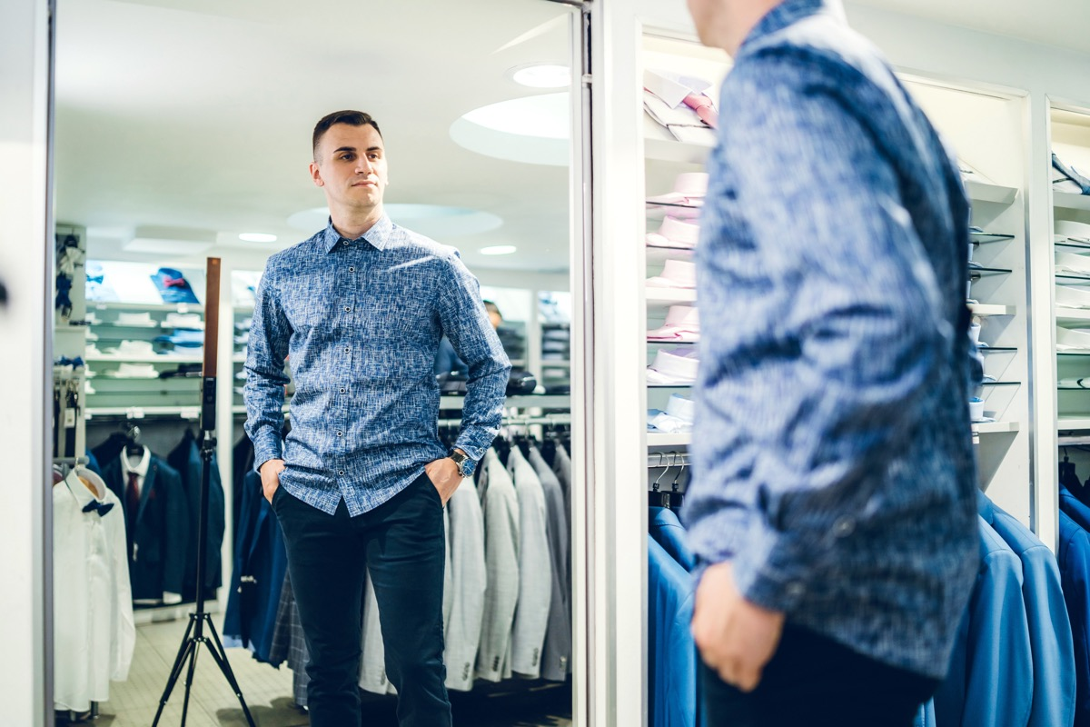 Young handsome caucasian man trying shirt in a store and looking himself in a mirror.
