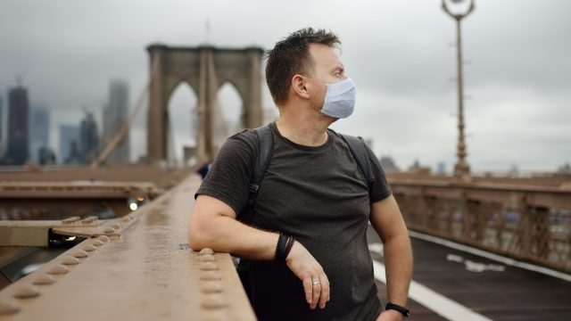 Man wearing a mask on dreary day in new york city