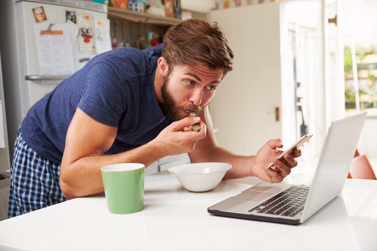 Man multitasking in the kitchen eating, standing, watching laptop, holding phone
