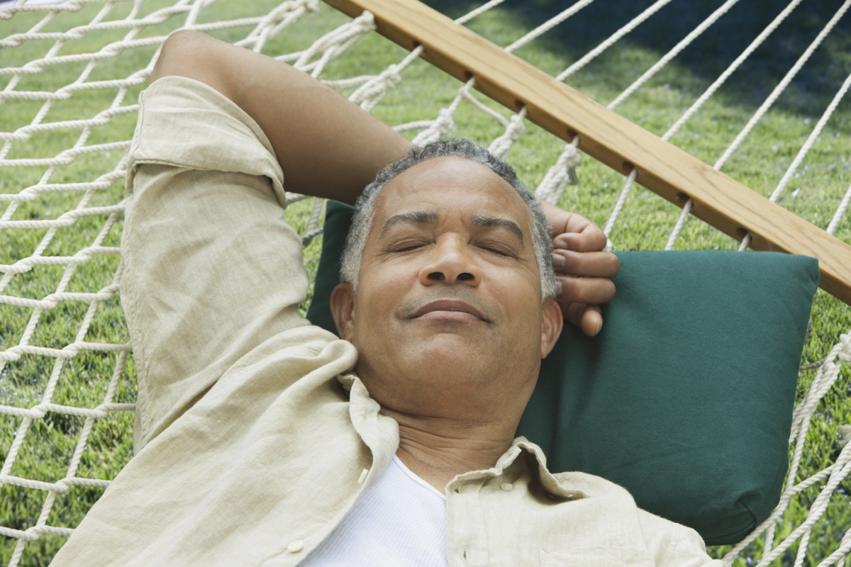 Older black man sleeping on a hammock