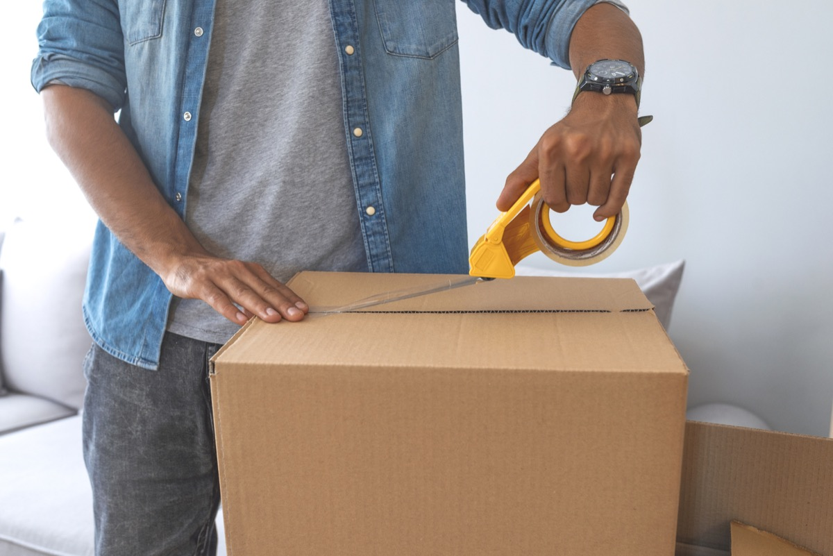 close up of male hand packing cardboard box, concept moving house. House moving concept. Happy young couple moving into new apartment with packaging boxes