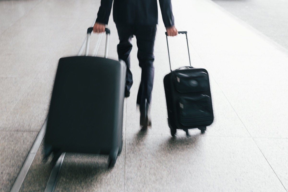 man running with two luggages