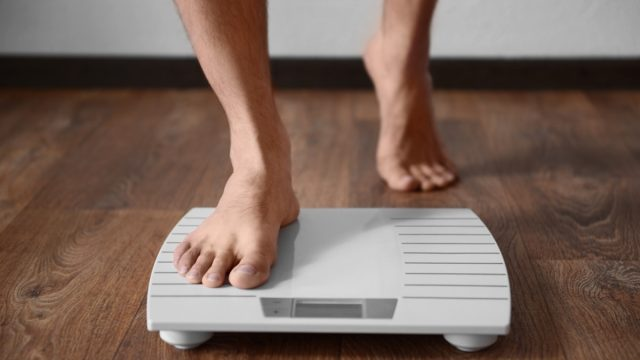 Man going on the scale looking at his weight