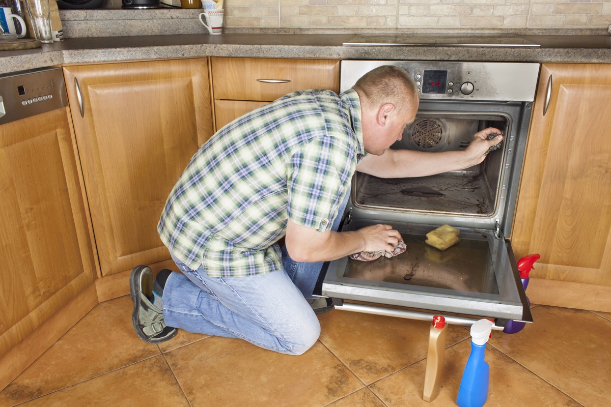 man scrubbing oven with steel wool